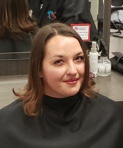 Woman smiles at the camera, while sitting in a beauty salon chair, sporting a new hairdo.