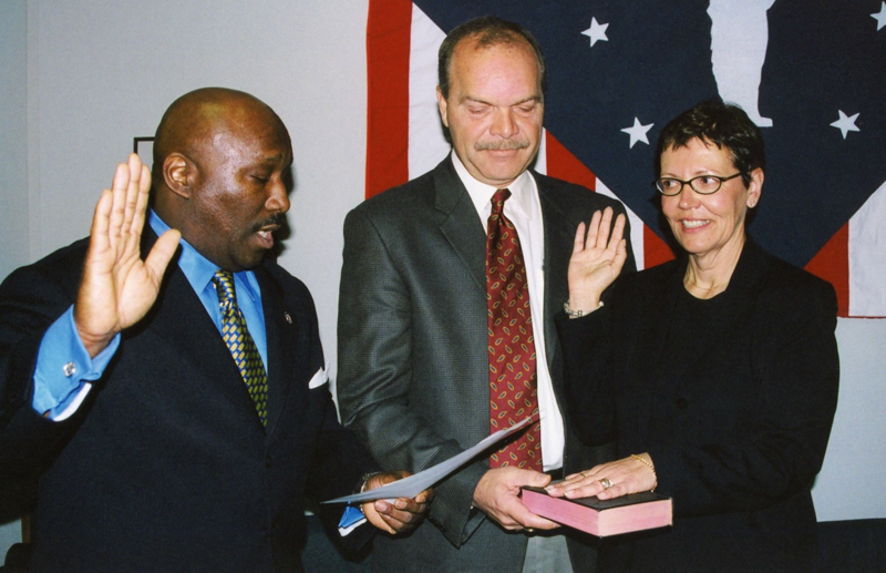 Two men swear-in a woman. Behind them is a flag. She is raising her right hand while her other hand is on a Bible.