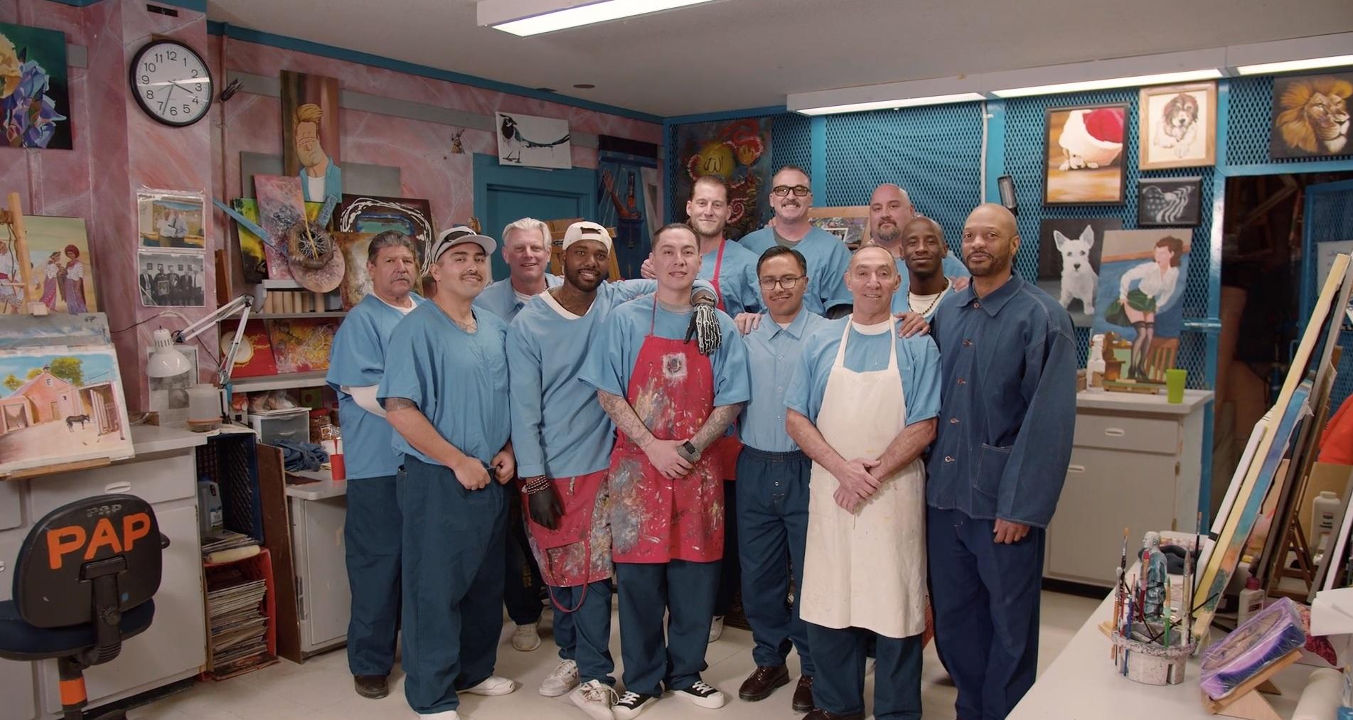 Men in blue stand in an art studio inside a prison.