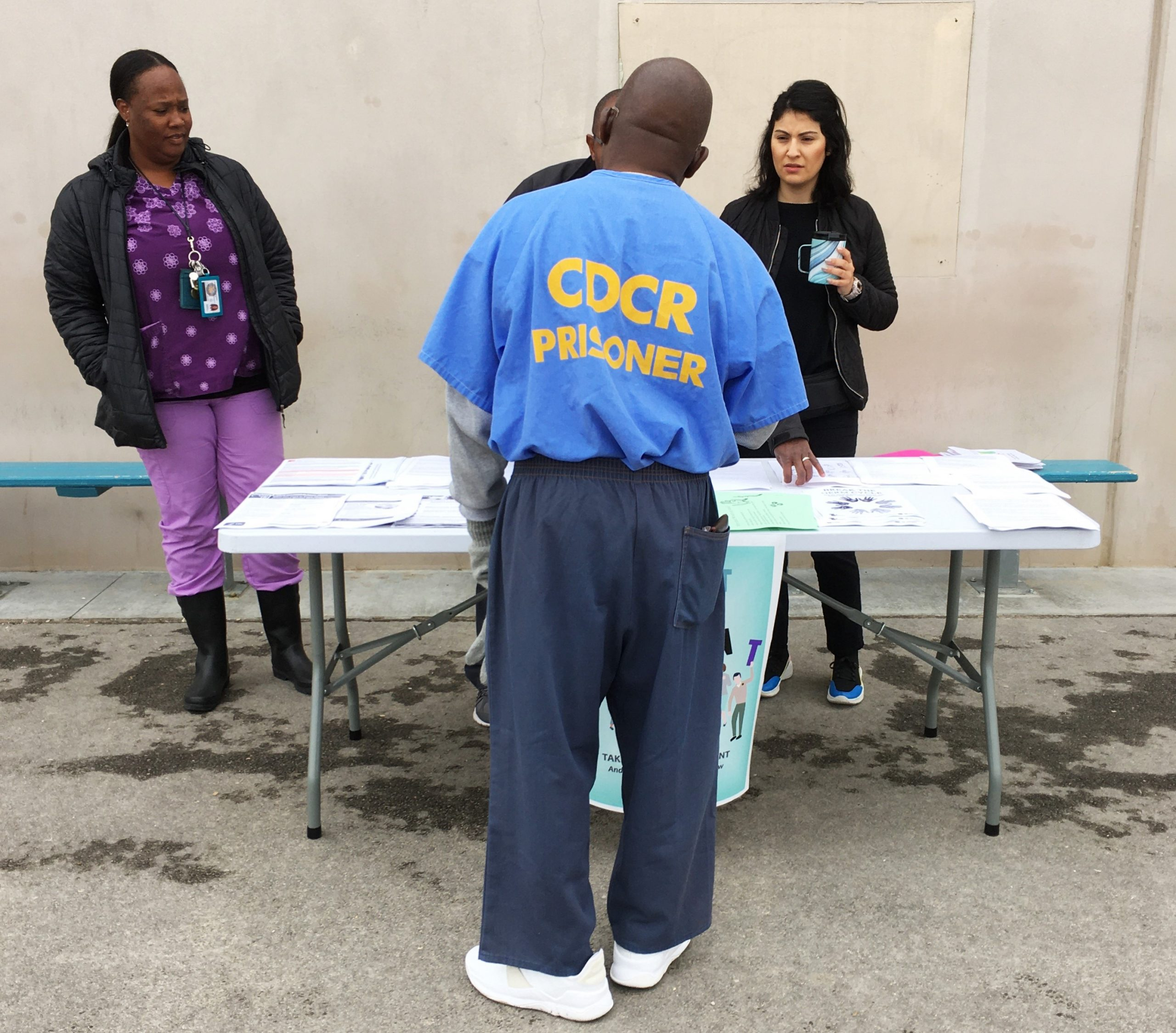 Prison inmate speaks to three people at an information booth.