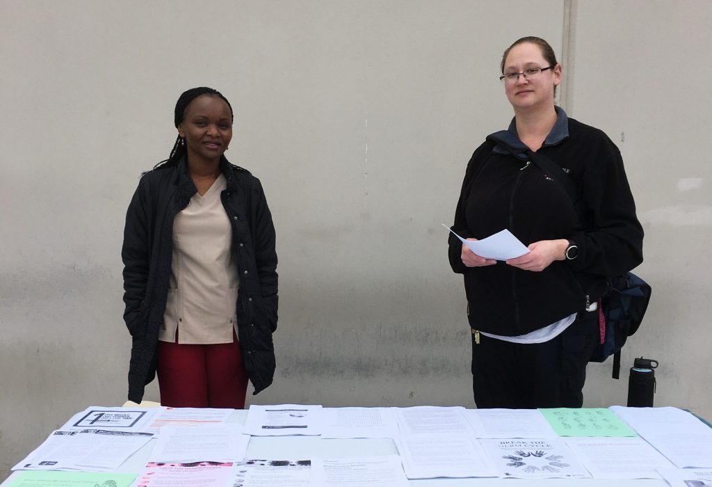 Two women stand at an information table in a prison.