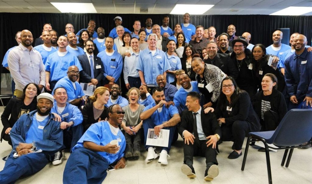 Men, women and inmates at California State Prison-Los Angeles County pose for a large group photo.