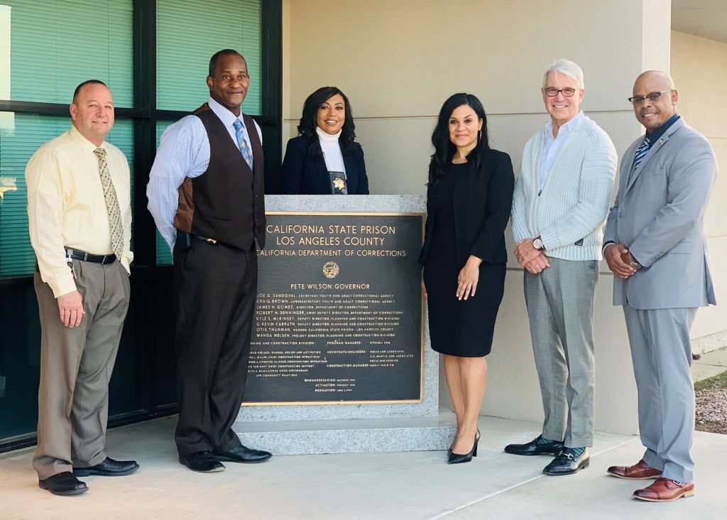 Four men and two women stand beside a plaque for California State Prison Los Angeles County.