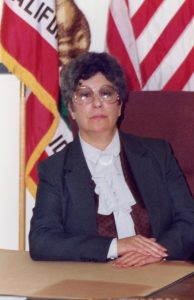 Woman sits at desk with flags in the background.