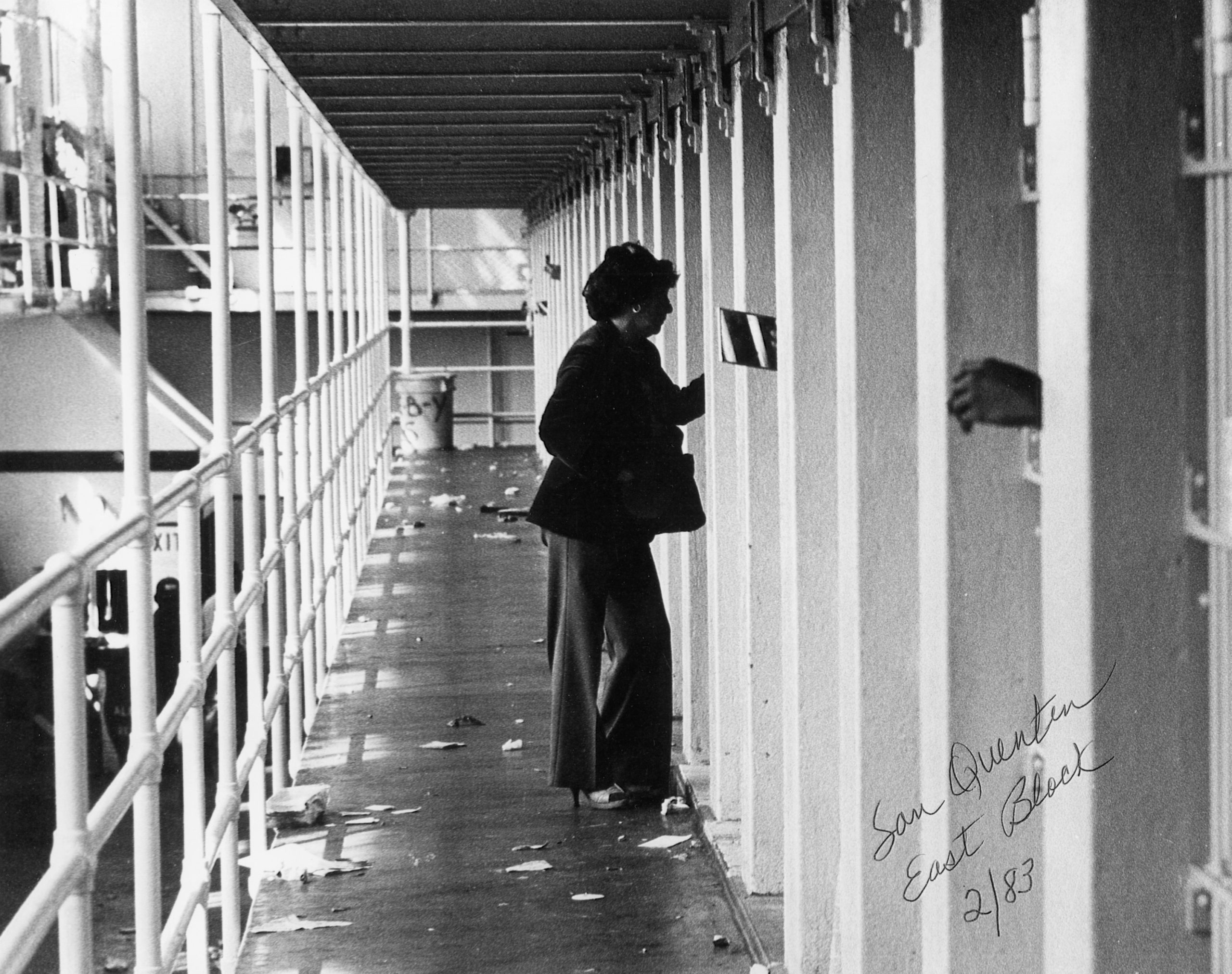 Woman speaks to an inmate through the bars of a cell door.