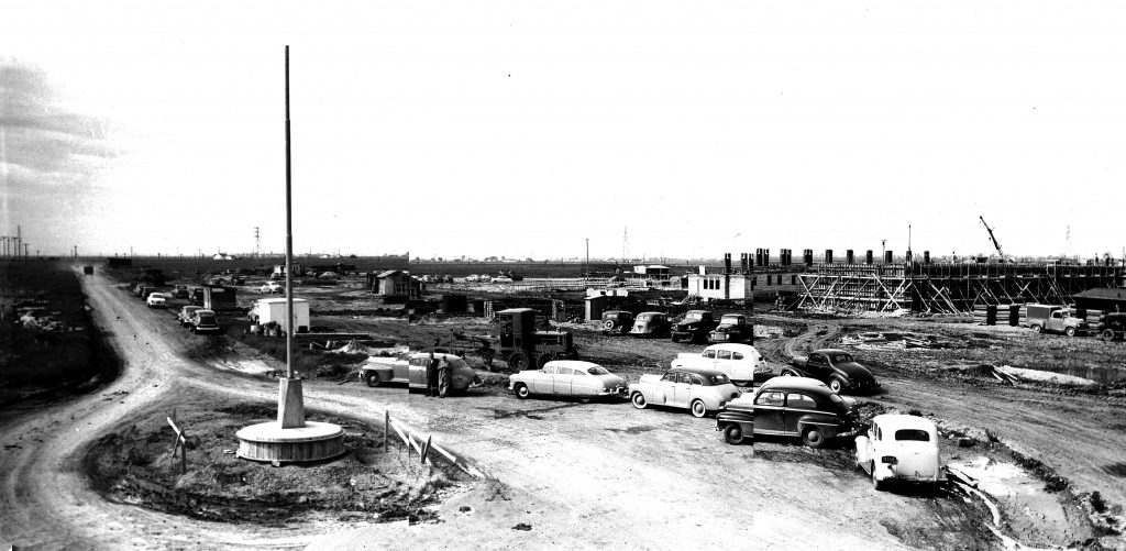Prison construction with vintage cars in a circular driveway.
