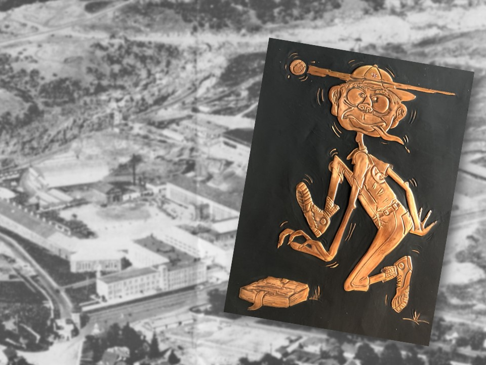A stamped piece of copper shows a cartoon character wearing a baseball uniform. In the background is an areal photo of Folsom Prison.