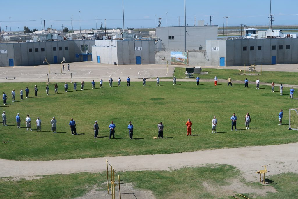 Large group stands on a yard in a prison.