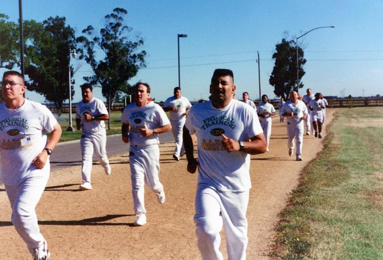 Men and women run around a dirt track.