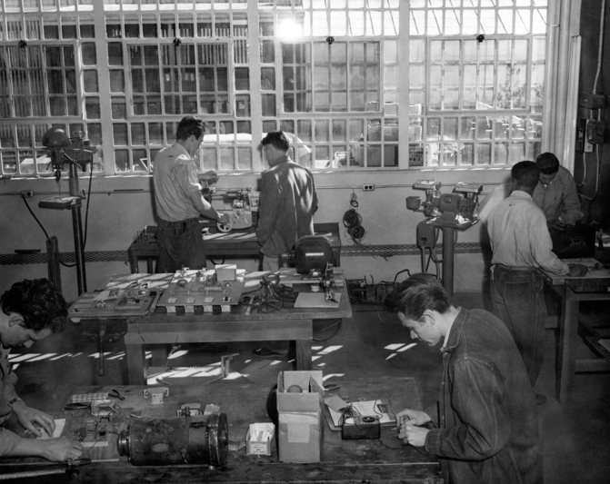 Four men learn machine repair in a prison. Large windows are behind them.