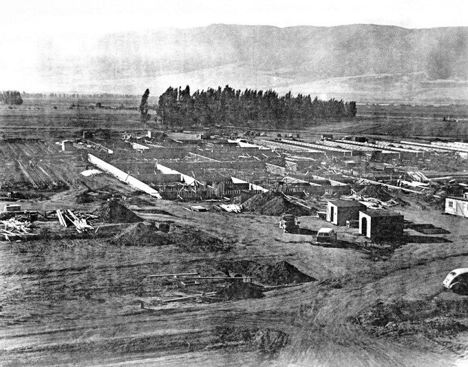 Construction of prison buildings in a large field.