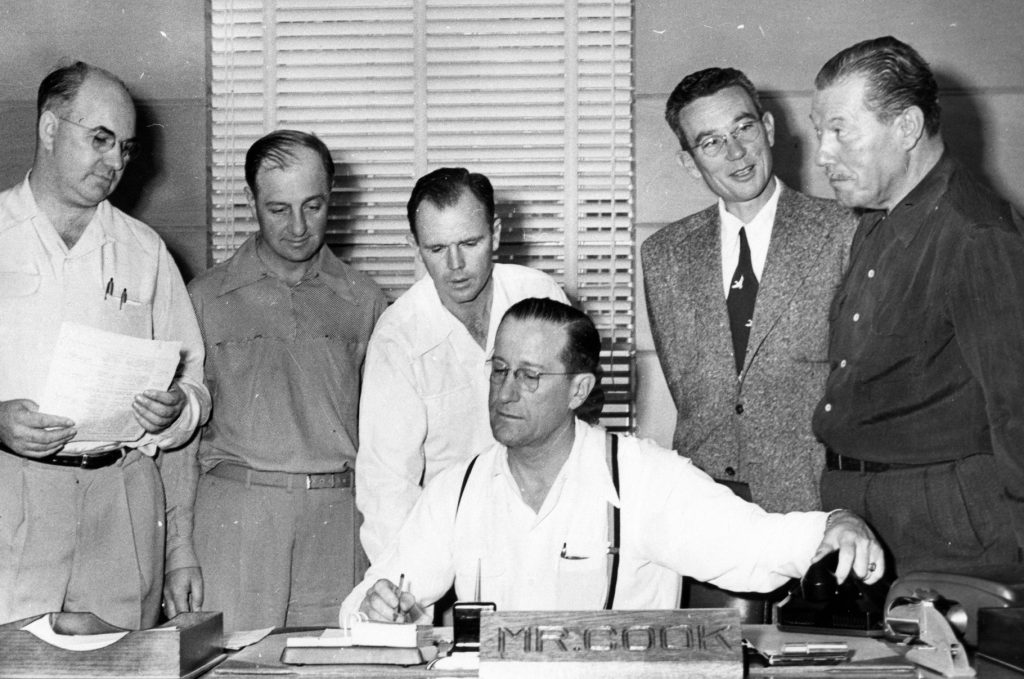 Sitting behind a desk, a man is about to pick up a telephone with other men stand around him and look on.