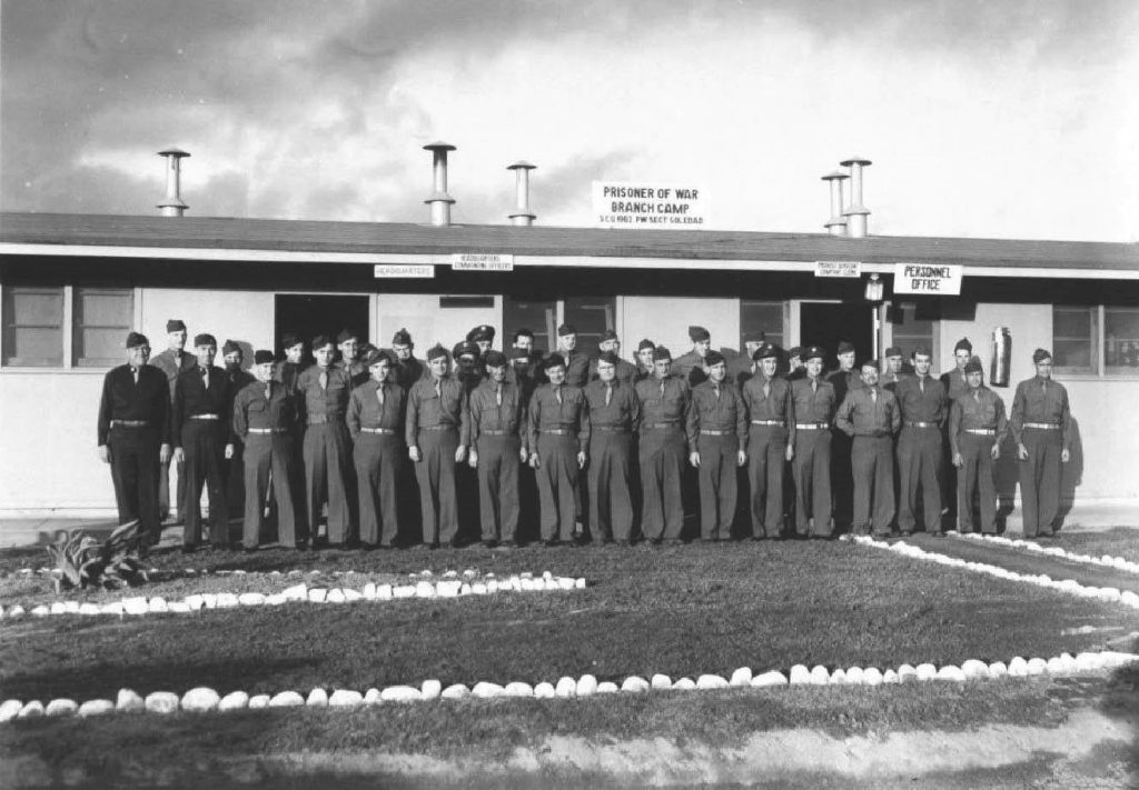 Men in military uniforms stand in front of a building.
