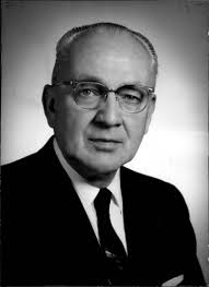Portait photo of man wearing glasses, jacket and tie.