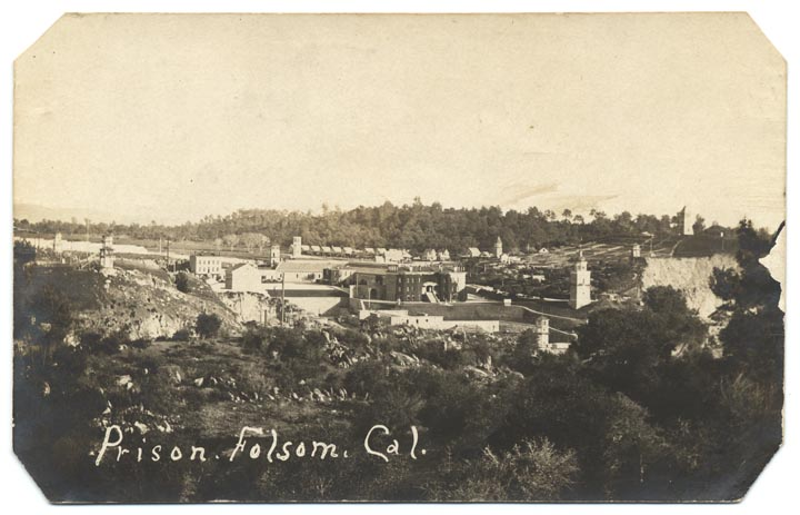"""Prison buildings surrounded by hills and trees. """"Prison, Folsom, Cal."""" is written on the image."""