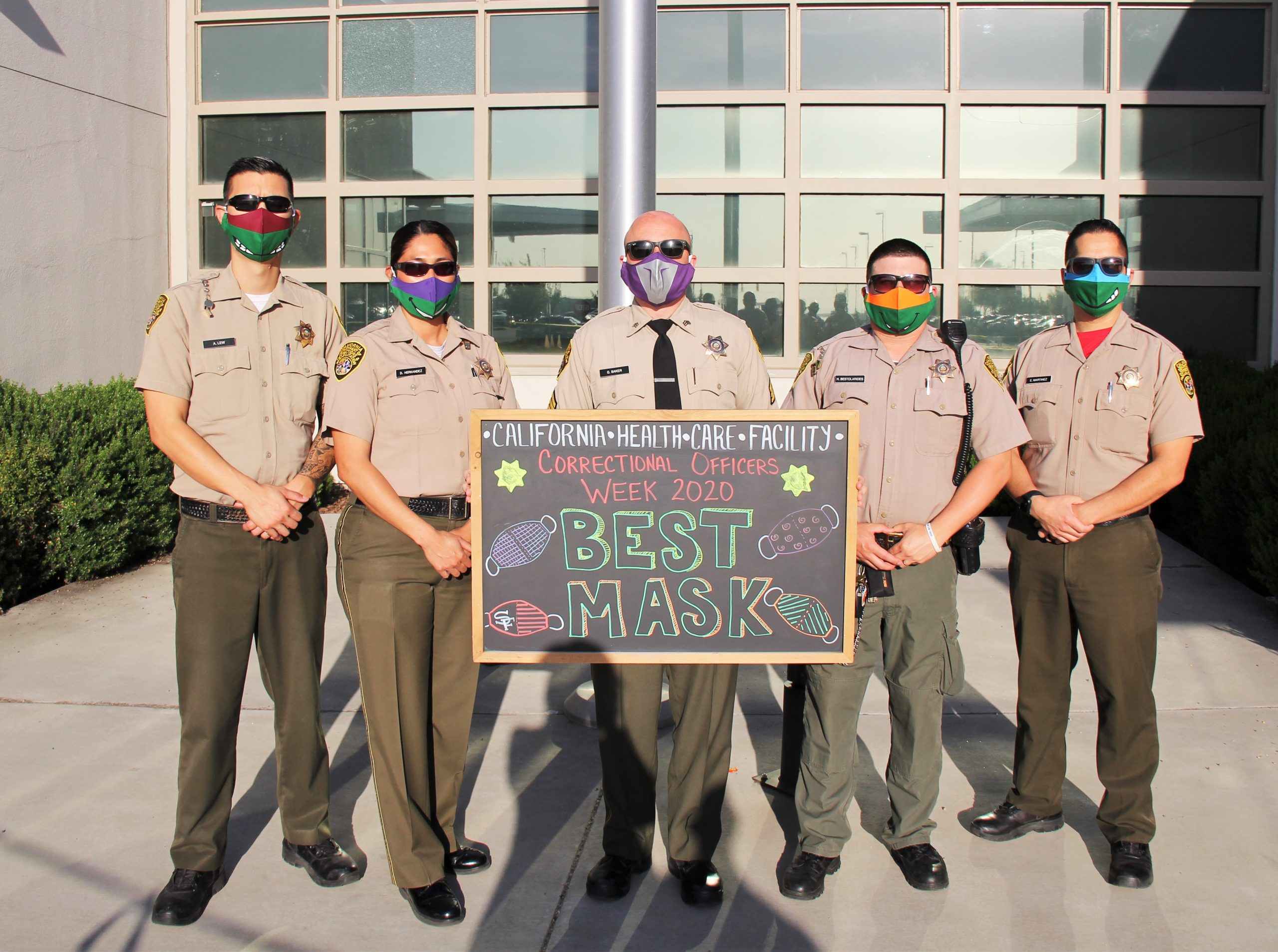 """Five correctional officers hold a sign saying """"best mask""""."""