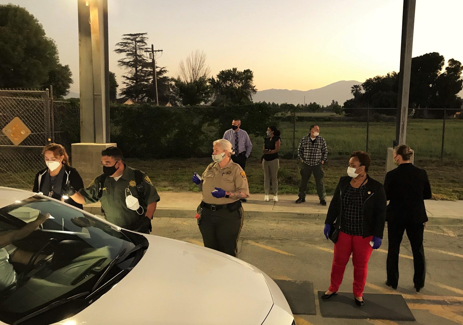 Men and woman wait at a prison entrance.