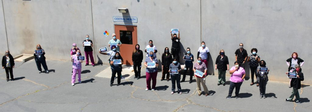 Prison staff hold thank-you signs outside a health office.