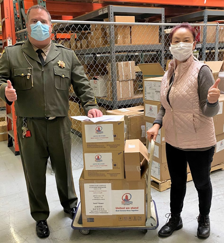 Correctional captain and a woman stand beside a stack of boxes.