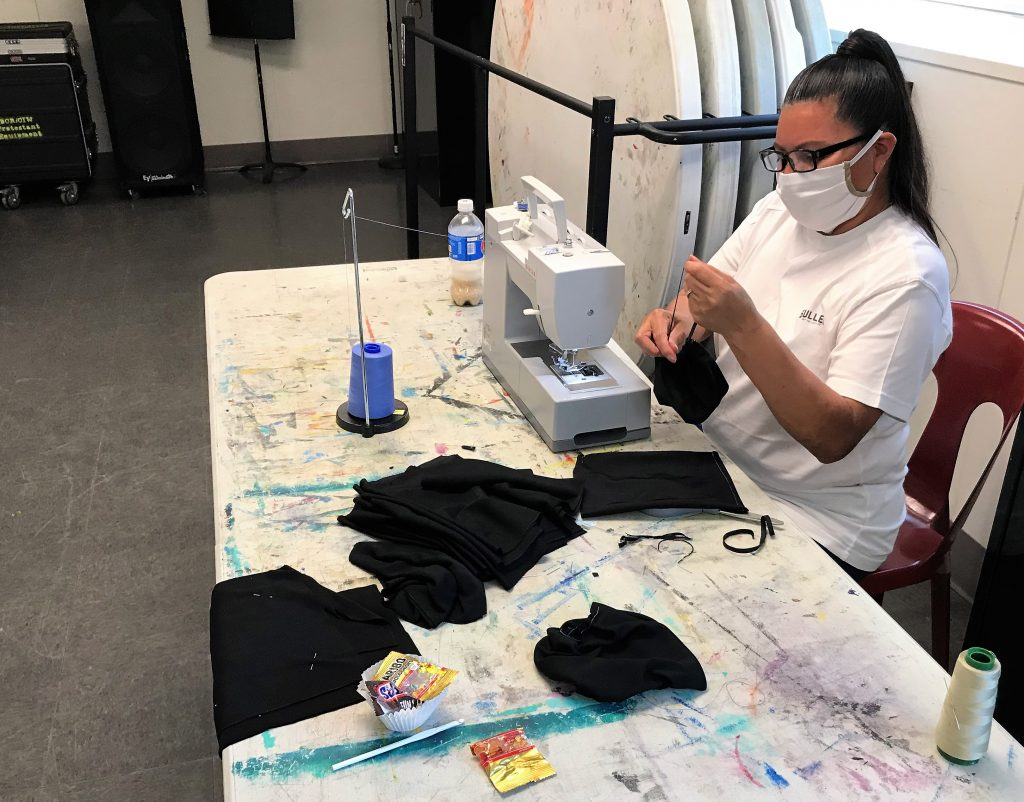 Woman wears mask while using a sewing machine.