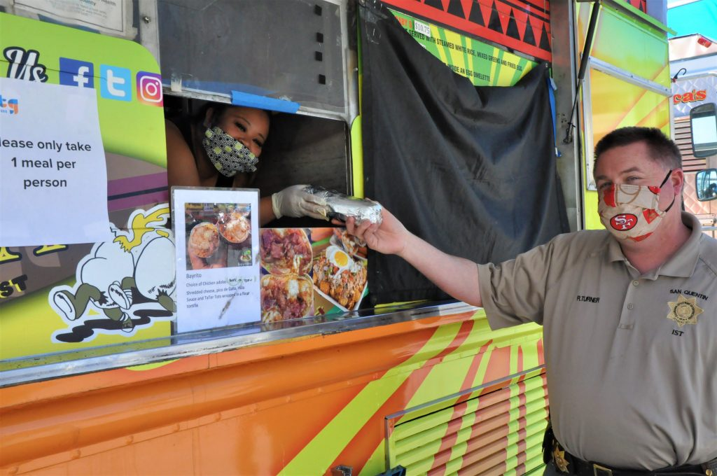 Officer wearing face mask takes wrapped food from a food truck.
