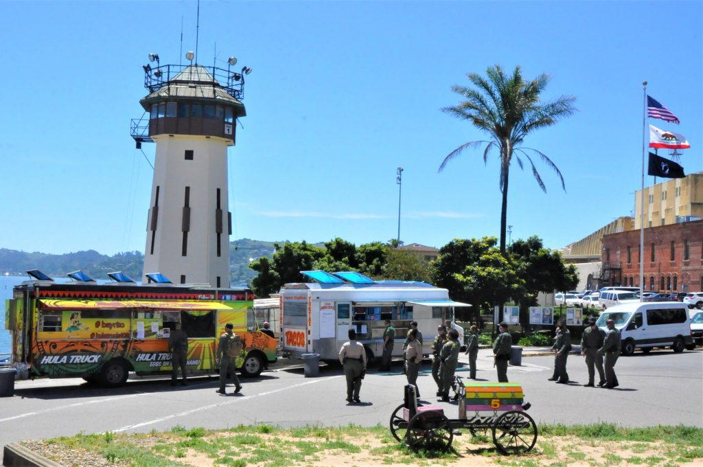 Men and women in uniform wait beside food trucks at San Quentin State Prison.