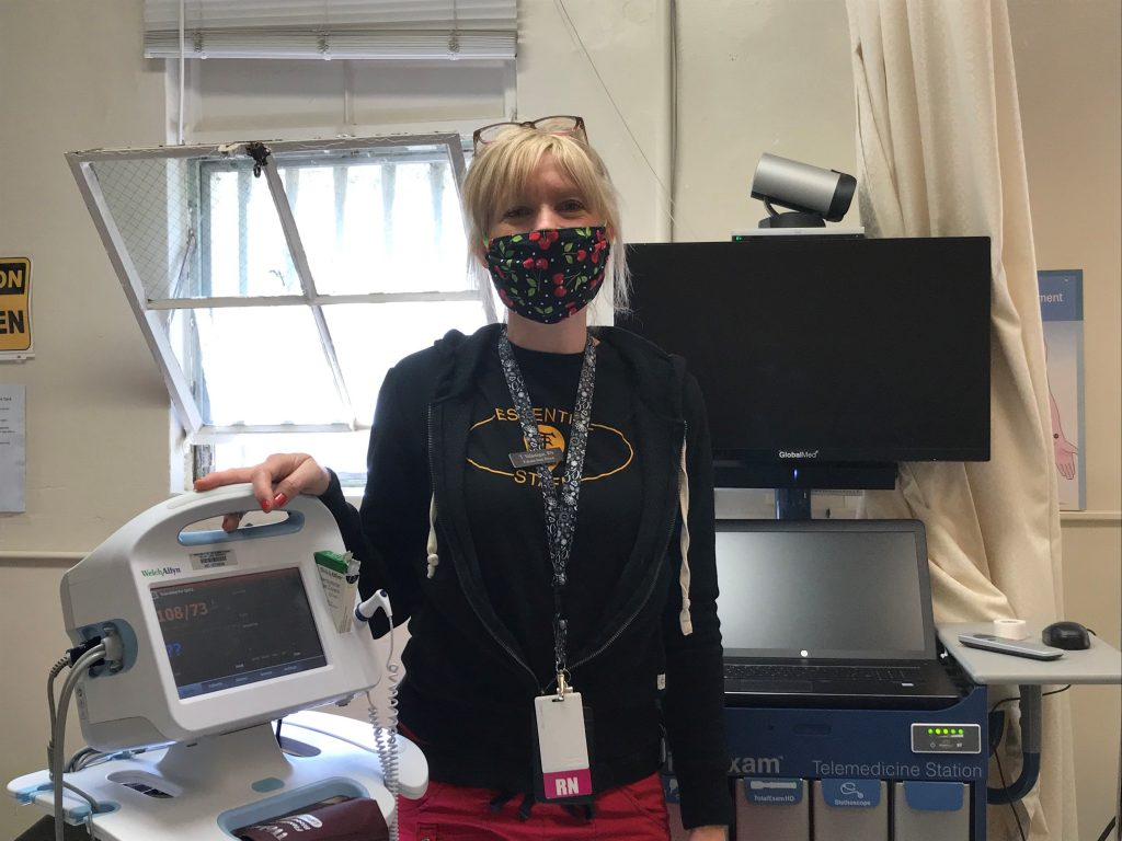 A nurse stands beside equipment while wearing a mask.