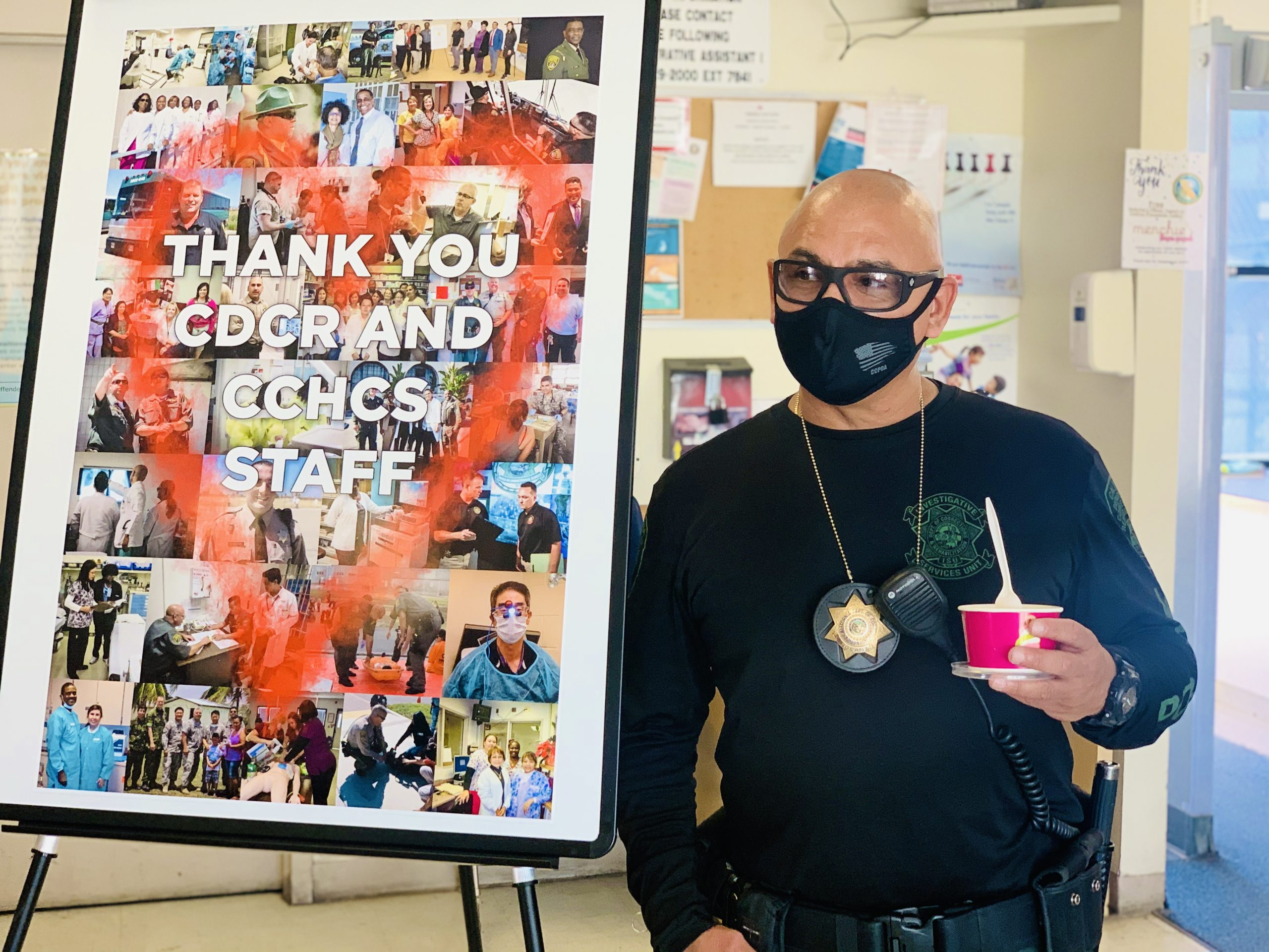 """Correctional sergeant holds frozen yogurt while standing beside a sign that reads """"Thank you CDCR and CCHCS staff."""""""