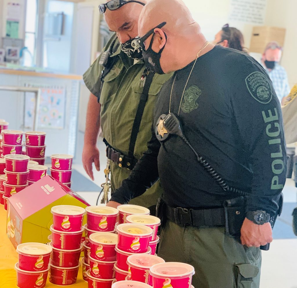 Two correctional sergeants look at a table full of frozen yogurt.