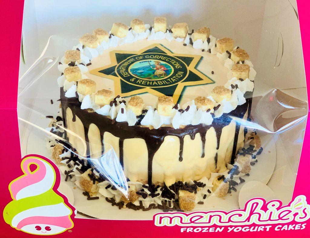 Frozen yogurt cake with CDCR badge on top.