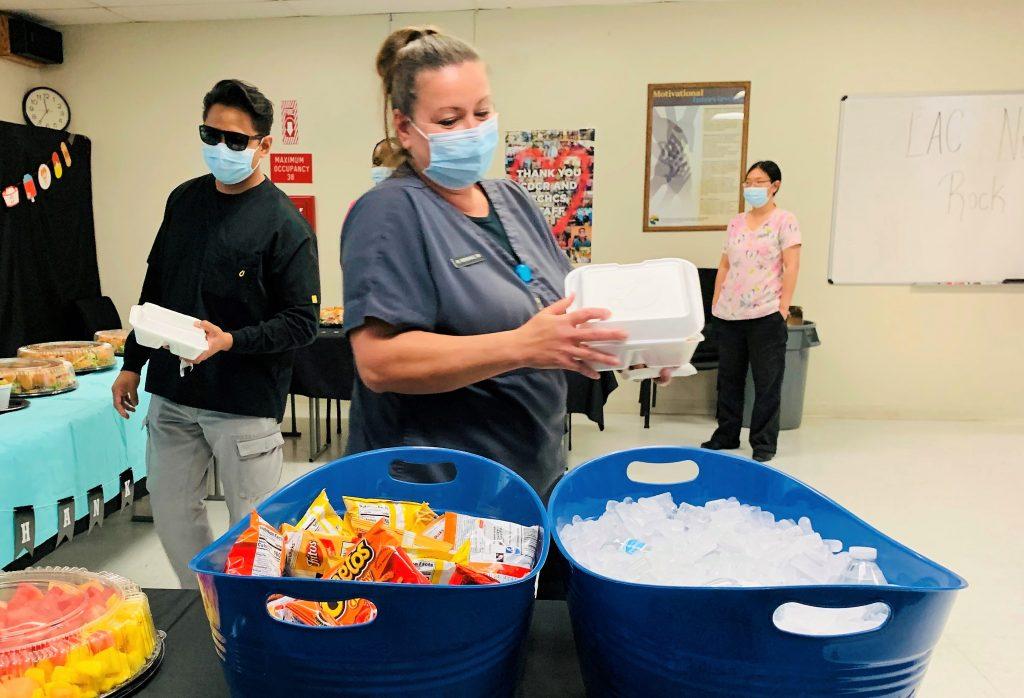 Nurses wait in line to get food.