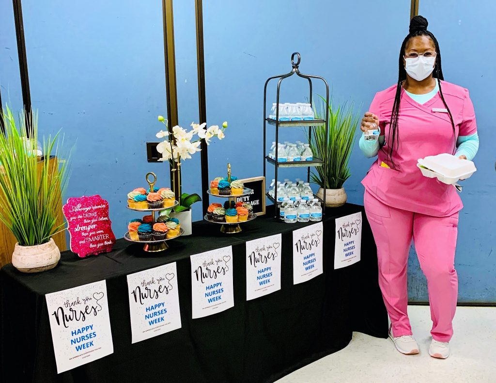 Prison nurse stands next to table of food.