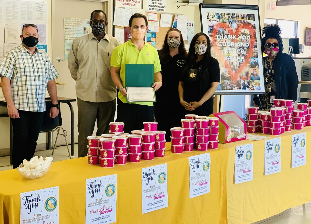 Five correctional employees and a business man stand behind a table full of frozen yogurt.