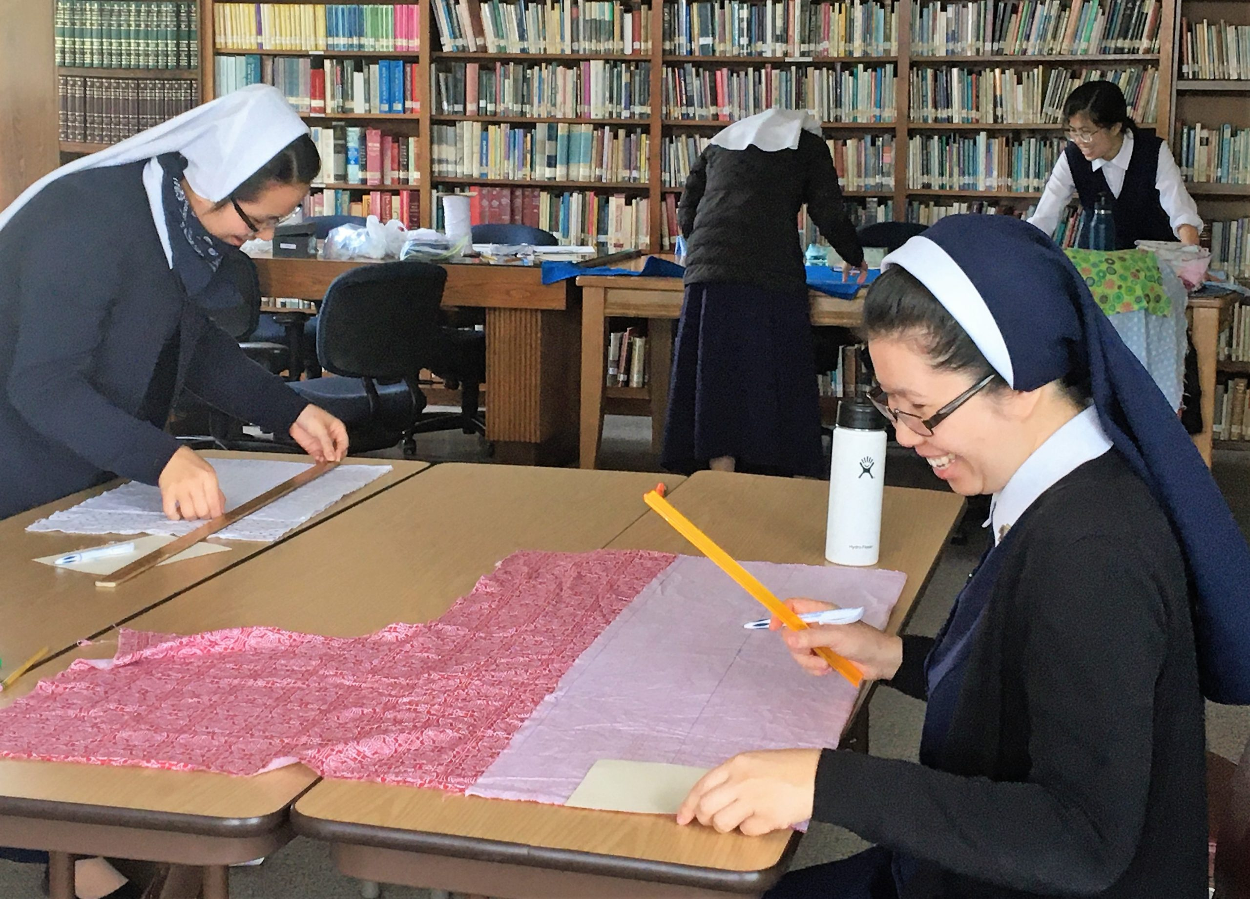 Nuns work in a library to make masks.