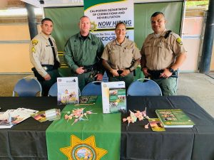 Three men and a woman in correctional officer uniforms stand at a booth.