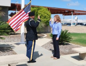 A woman stands in front of a military officer. Both have their right hands raised while a U.S. flag waves beside them.