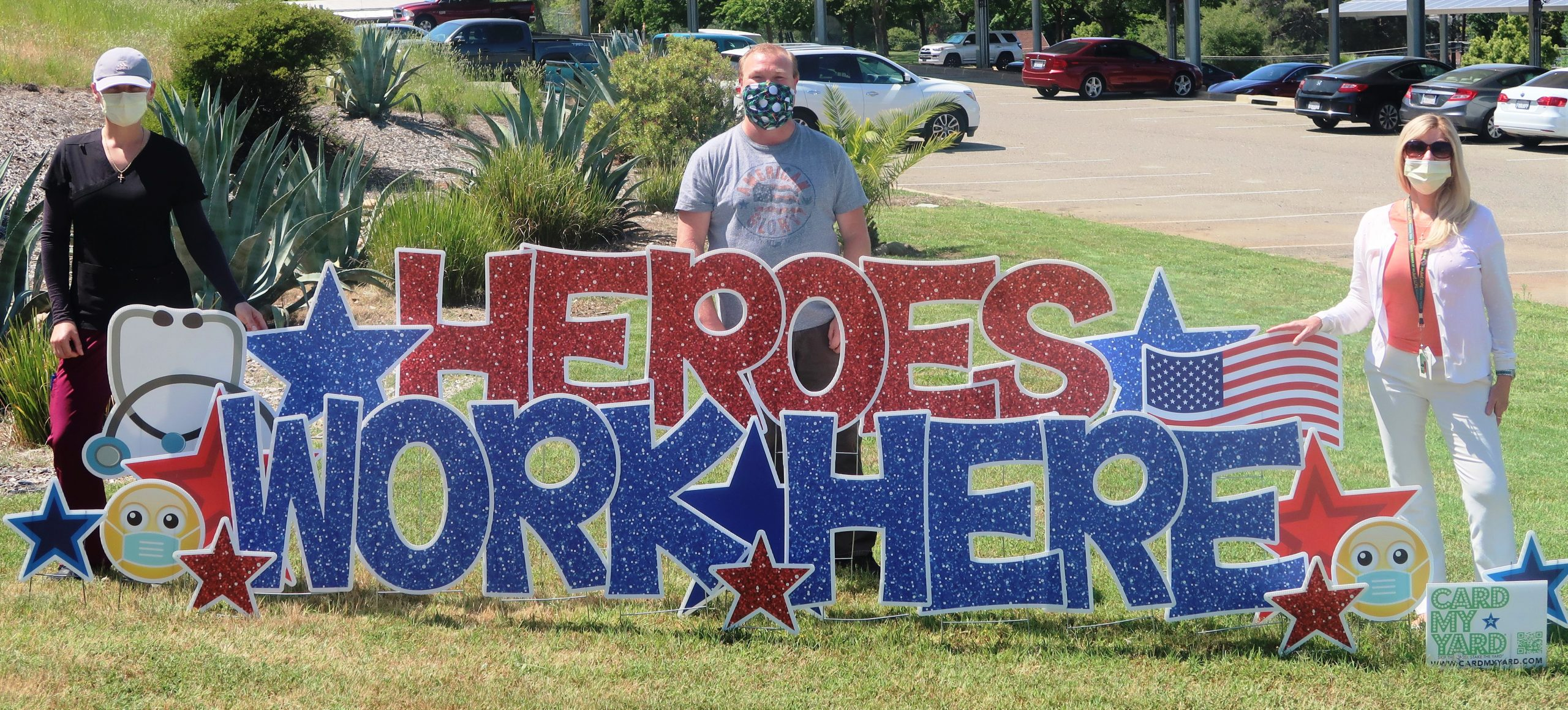 Photo of a man and two women wearing masks behind a sign that states: Heroes Work Here