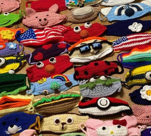 Photo of crocheted masks of different colors, characters and sizes.