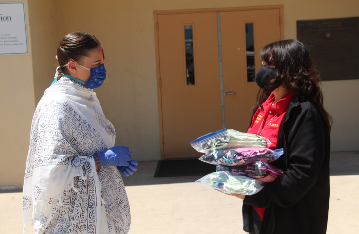 Two women wearing masks stand apart while exchanging a package.