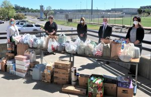 Five people stand behind a table full of food donations.