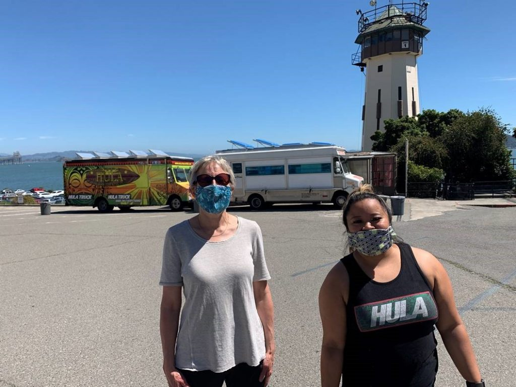 Two women in masks stand in front of two food trucks at San Quentin prison. A tower can be seen behind them.