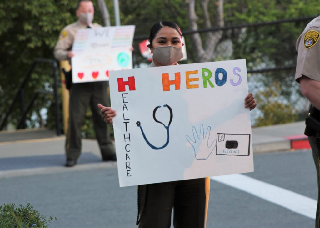 Correctional officers hold signs thanking hospital medical staff.