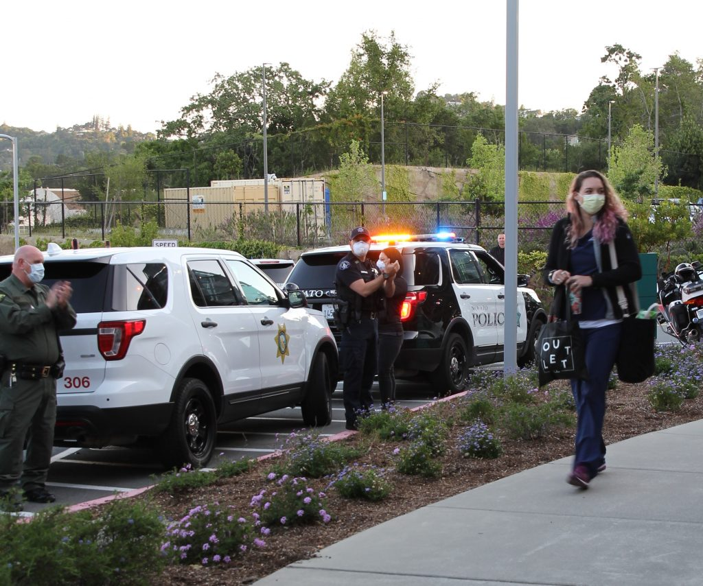 CDCR vehicle and other police cars with lights on as woman walks by on sidewalk.