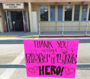 """A sign in front of California Men's Colony says """"thank you for being a front line hero."""""""