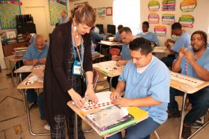 Teacher hovering over inmate in classroom setting
