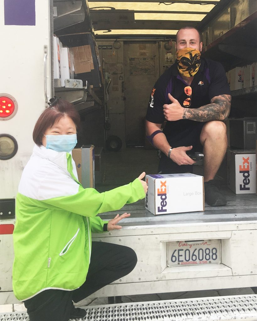 Woman wearing mask gives a thumbs-up as a delivery company employee sits in a truck.