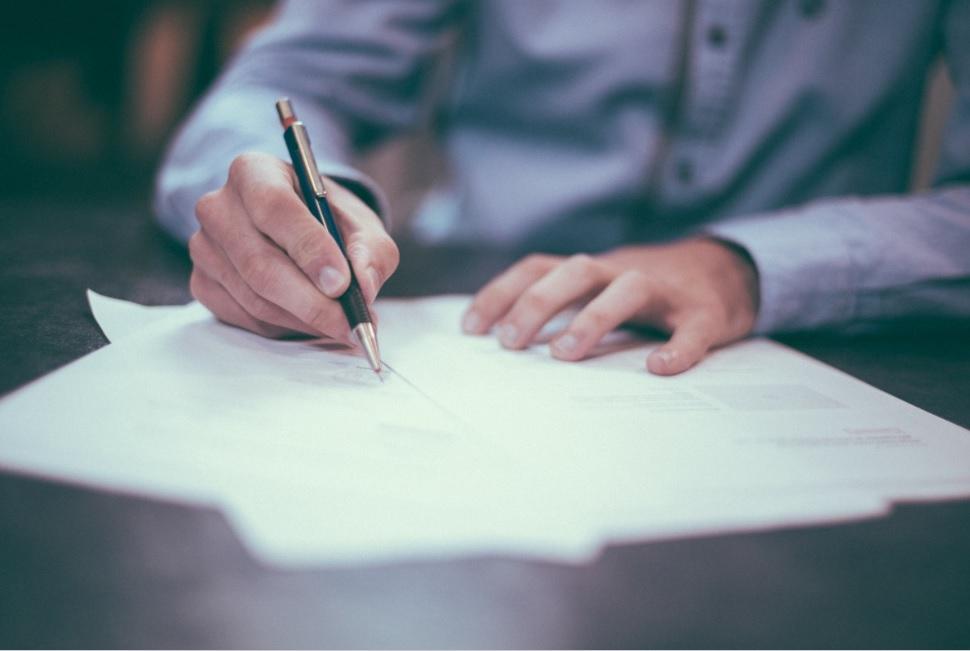 A man signs paperwork.