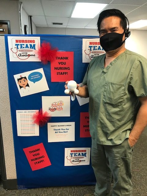 """Man nurse stands in front of posters that say """"thank you."""""""