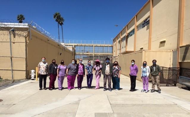 Nurses in scrubs stand in a prison.