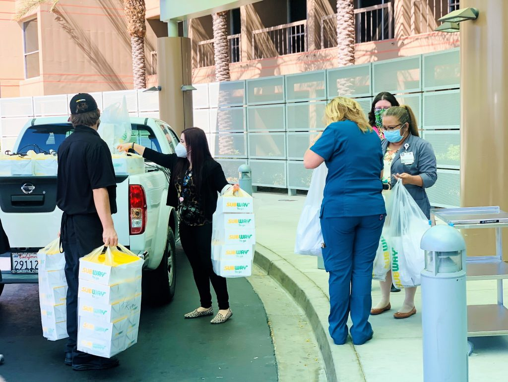 Men and women get lunch bags from Subway sandwich shop, unloading them from a truck.